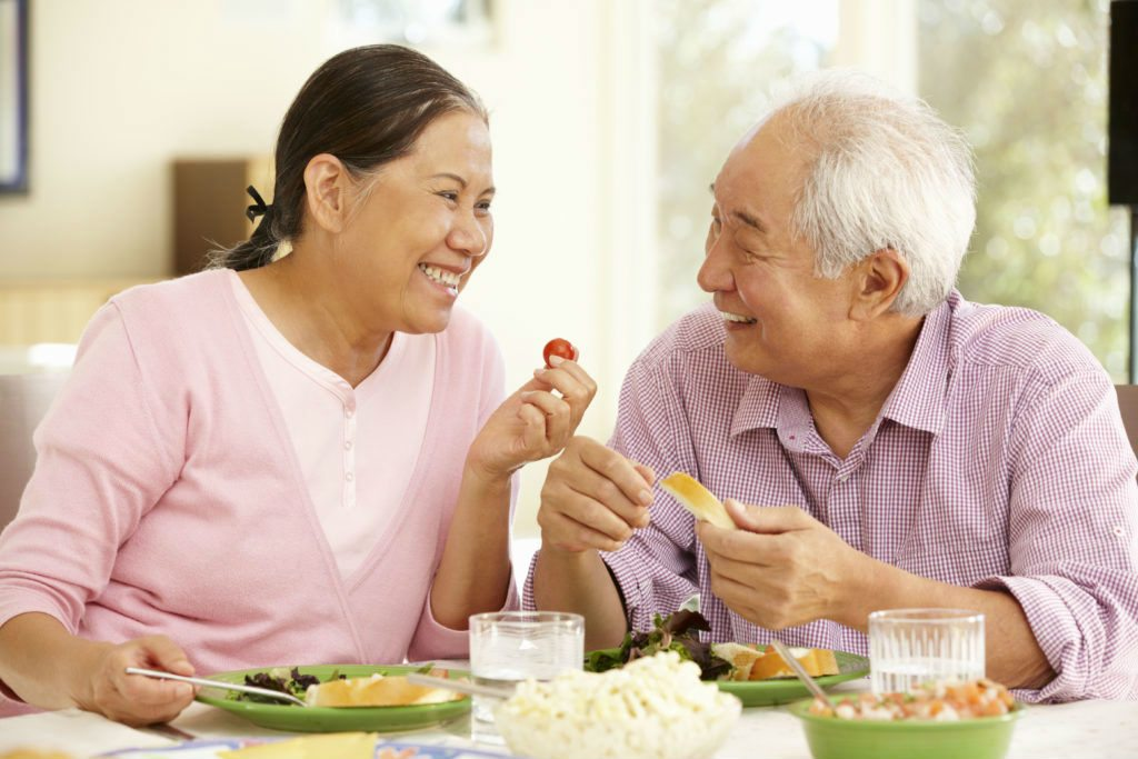 Elderly Asian couple enjoying their food with no chewing issue because of their dental implants.