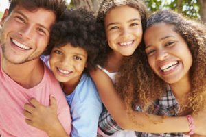 Mixed race family of 4 hanging out with healthy smiles from good oral health care.