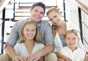 Family of 4 sitting on stairs smiling with healthy bright smiles.
