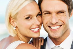 Couple smile at results from full-mouth rehabilitation at Uptown Guelph Dental.
